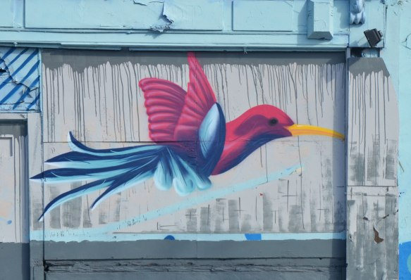 mural of a blue and dark pink bird in flight, with a long yellow beak