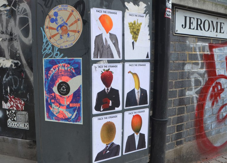 stickers and paste up street art on a metal box and wall on a street corner including 6 posters by Face the Strange where men's portraits have fruits instead of heads, orange, grapes, strawberry, banana, and apple. Two other paste ups as well.