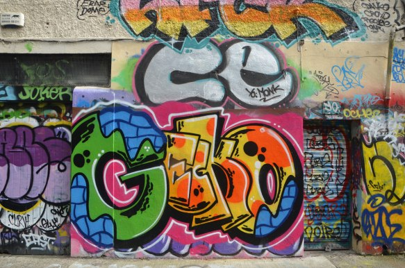 large colourful tag that says gecko on a wall with other tags