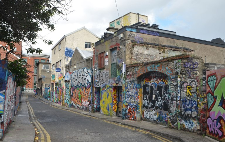 a narrow street with low buildings on both sides, walls of which are covered with graffiti