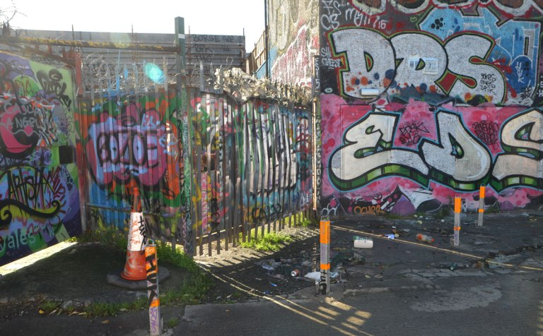 graffiti and street art on fences, with sunlight shining through