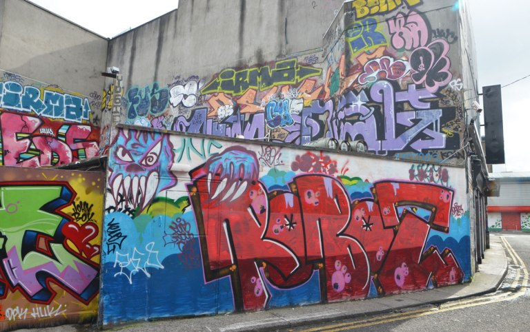 a lot og graffiti and tags on concrete walls and fence including a large red roboz tag