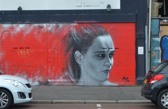 mural by emic, head and face of a young woman looking to the right, in grey tones (black and white) on a bright red background.