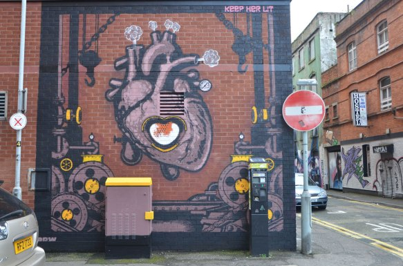 a mural of an anatomical painting of a heart with the center being a furnace, steam puffs coming out of the vessels at the top, words at the top of the mural are Keep Her Lit