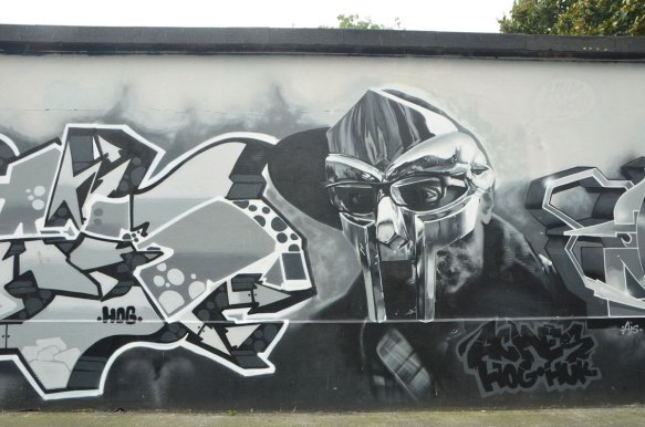 grey tones mural of a man in a mask with text street art on either side of his head and shoulders, words say aches hog huz