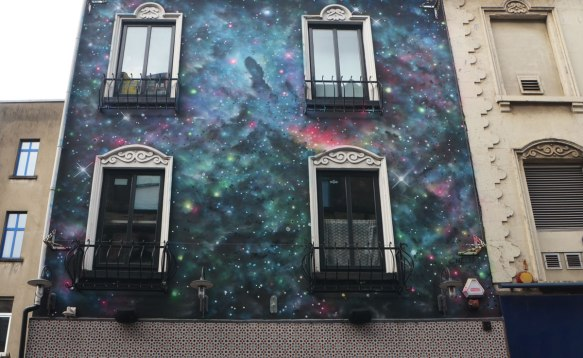 The front of a house, upper storeys, covered with a painting that looks a bit like an imaginative version of the stars at night. The universe and beyond.