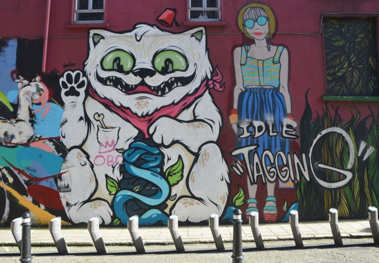part of a mural, a woman standing wearing blue skirt and green top and sunglasses. Also a large white sitting cat with one paw raised.