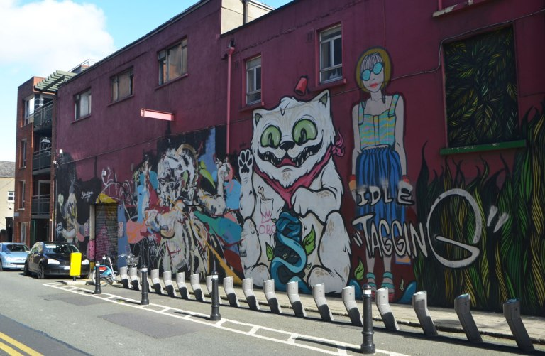 large mural on a maroon wall, titled Idle Tagging, a woman standing, a large white cat, plus other creatures,