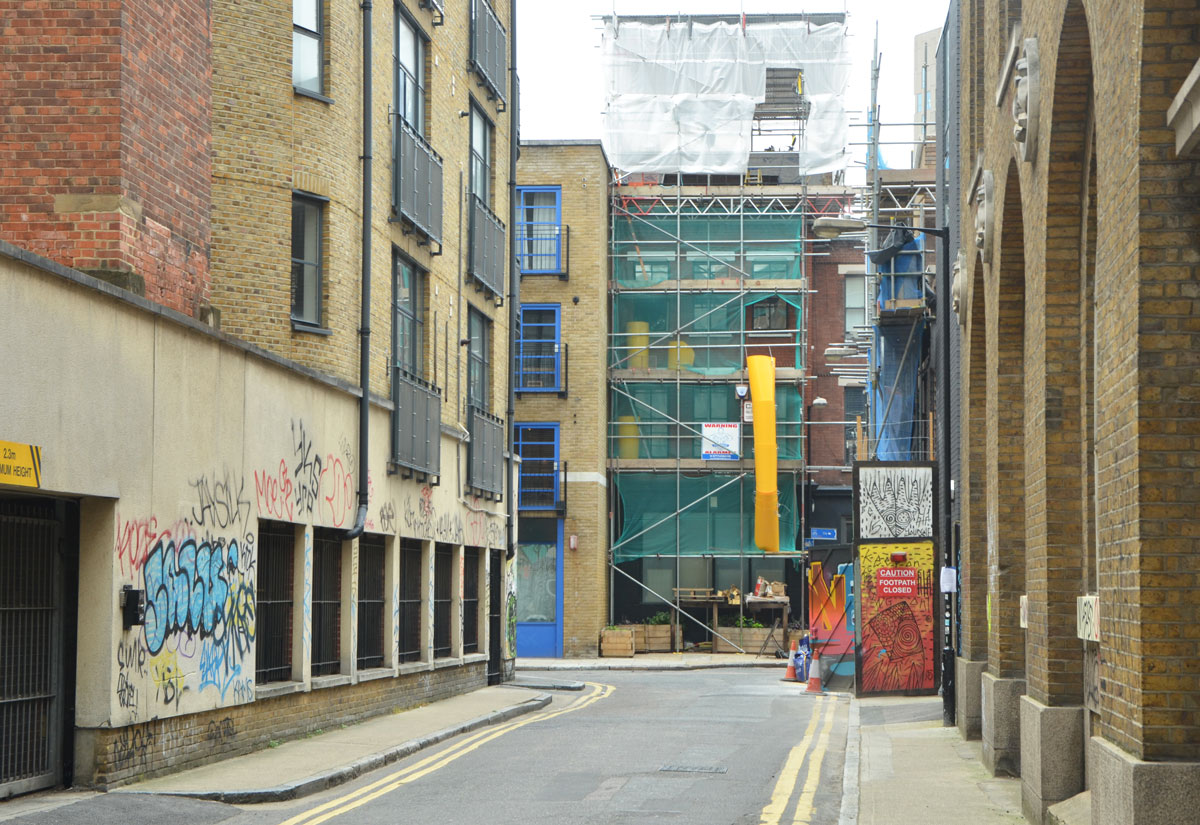 looking down a short narrow street with three or four storey brick buildings on either side, construction of a building at the end of the street, covered with green netting on the bottom, and white plastic on the top