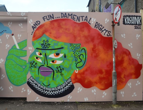 mural by Kashink of person with green face, four eyes and long bushy reddish orange hair. Words say and fun--damental rights. Person is smoking (green hands)