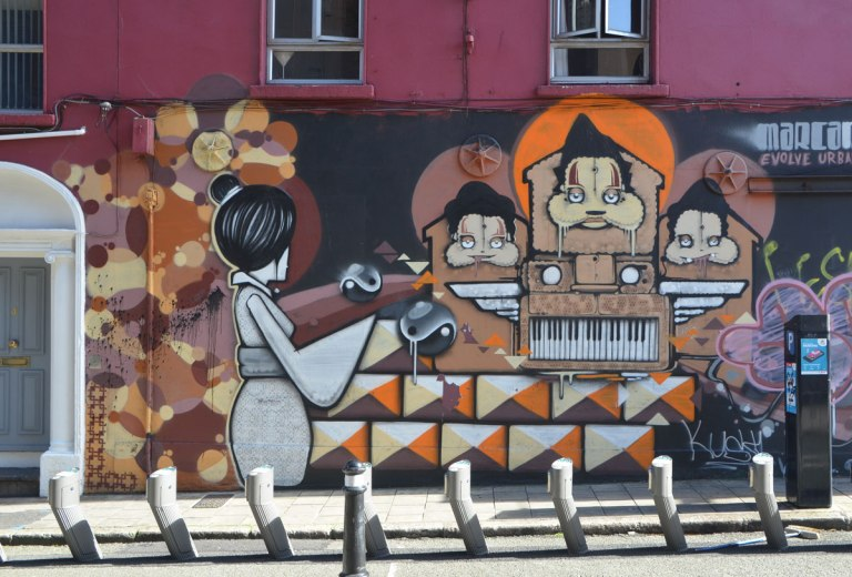 mural on the side of a building, a Japanese looking woman, a keyboard with wings, in orange and brown.