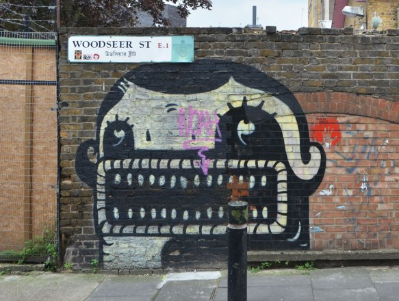 painting by street artist plin of a black and white face that is mostly mouth - a large rectangular mouth with a lot of little teeth, two eyes and only a small bit of black hair. On a brick wall by a sign (street sign) that says Woodseer St. E.1. It also has the name in arabic.