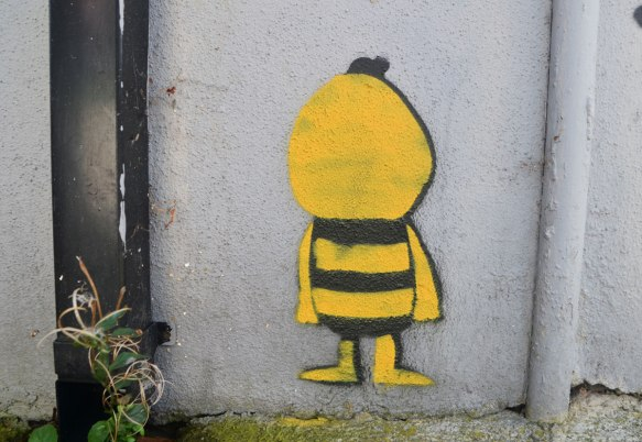 little street art painting of a yellow and black little guy with face towards the wall (or is faceless)