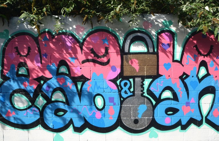 graffiti that says angela & caolan. Angela is in pink letters and caolan is in blue. the e in angela is a lock and the L in caolan is a key. The key fits into the lock.