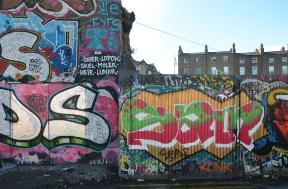 graffiti and street art on building and fence, with brick rowhouses behind, Dublin