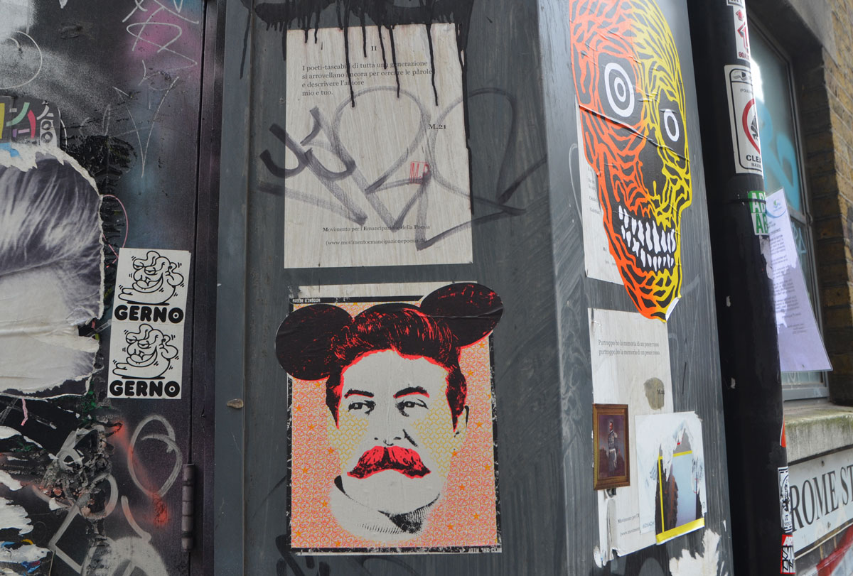 many pieces of street art, including a man wearing mickey mouse ears, a large grinning skull in yellow and orange, and poems written on posters in Italian.