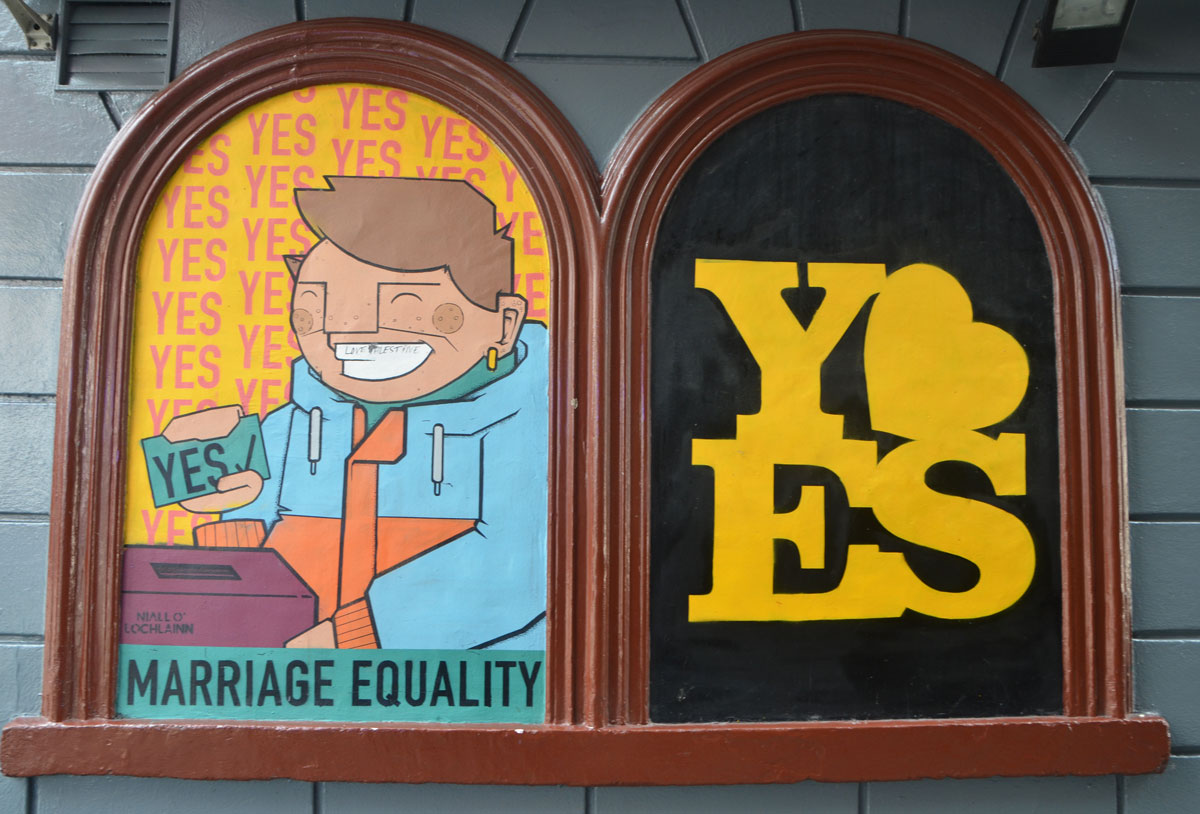 two adjoining window shapes with brown frames and rounded tops. On the left a picture of a man voting yes with the words marriage equality. On the right the word yes in yellow with a yellow heart.