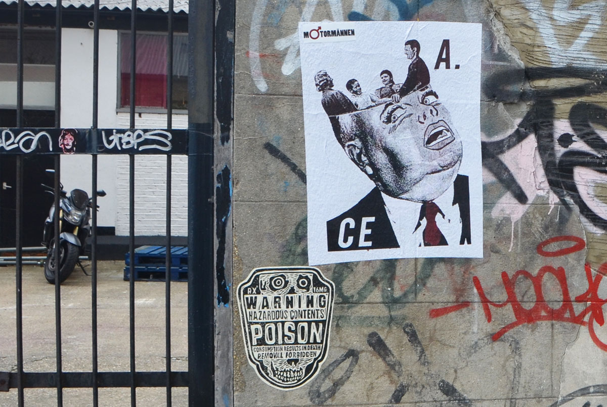 a brick wall beside a metal gate, behind the gate is a motorcycle, on the brick wall are two street art paste ups, a warning poison label and a poster by M. Torannen of a man with the top of head opened up and four people standing inside.