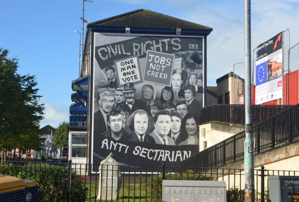 Free Derry mural in Bogside, Derry Northern Ireland, in shades of grey, commemorating Bloody Sunday in 1972 - civil rights and anti-sectarian, pictures of people with placards who marched in a peaceful demonstration
