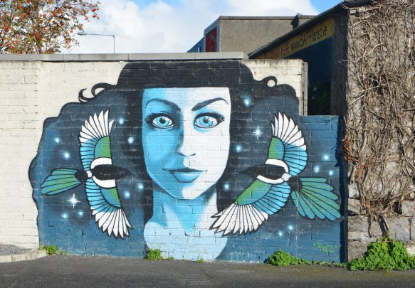 a mural of a woman in blue tones, frontal image, staring straight ahead. Two birds are in flight, one on either side of her, flying towards the center of the picture