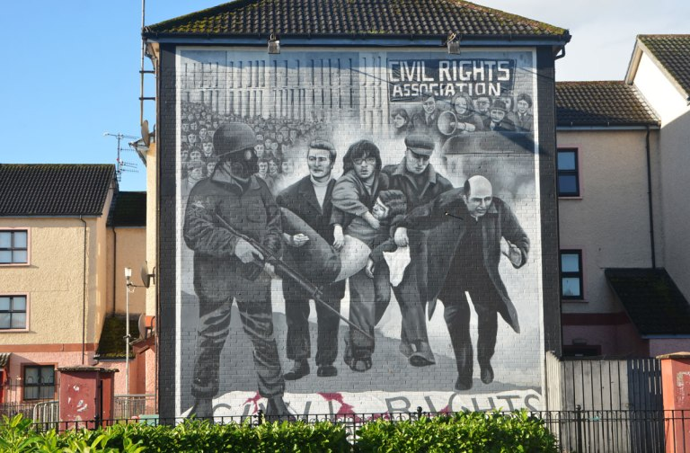 Free Derry mural in Bogside, Derry Northern Ireland, in shades of grey, commemorating Bloody Sunday in 1972 - a priest with his head down carries a white flag as people carry an injured man