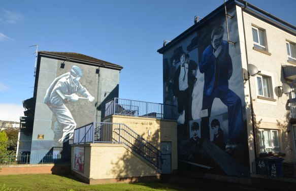 Free Derry mural in Bogside, Derry Northern Ireland, in shades of grey, commemorating Bloody Sunday in 1972 - two murals on the sides of two buildings, one is a soldier breaking down a door and the other is people marching in a demonstration but running away from tear gas