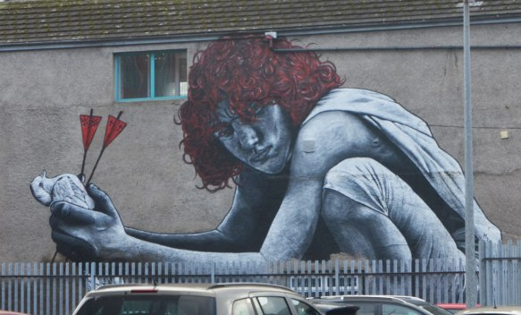 mural of a red headed young man squatting and holding a dead bird in his hands. The bird has two arrows through it, with red ends on the arrows. The mural looks to be on top of a fence and there are cars parked in front of the fence
