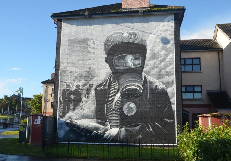 Free Derry mural in Bogside, Derry Northern Ireland, in shades of grey, commemorating Bloody Sunday in 1972 - a man wears a gas mask