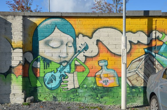 mural, stylized painting of a person playing a blue guitar with a cloud in the background, yellow sky, and a bottle of something floating beside the musician