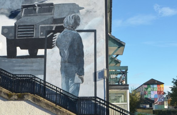 Free Derry mural in Bogside, Derry Northern Ireland, in shades of grey, commemorating Bloody Sunday in 1972 - man with back to viewer watches a tank. Second mural in the background of a white outline of a peace dove over a chequer board design in many different colours.