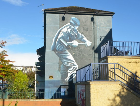 Free Derry mural in Bogside, Derry Northern Ireland, in shades of grey, commemorating Operation Motorman in 1971- a British soldier breaking down a door in Derry