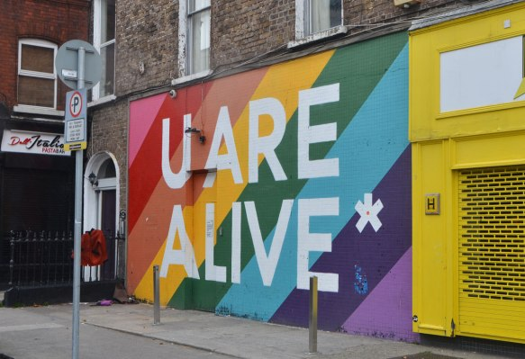 mural, diagonal rainbow stripes for the background, large white letters for the words U are alive