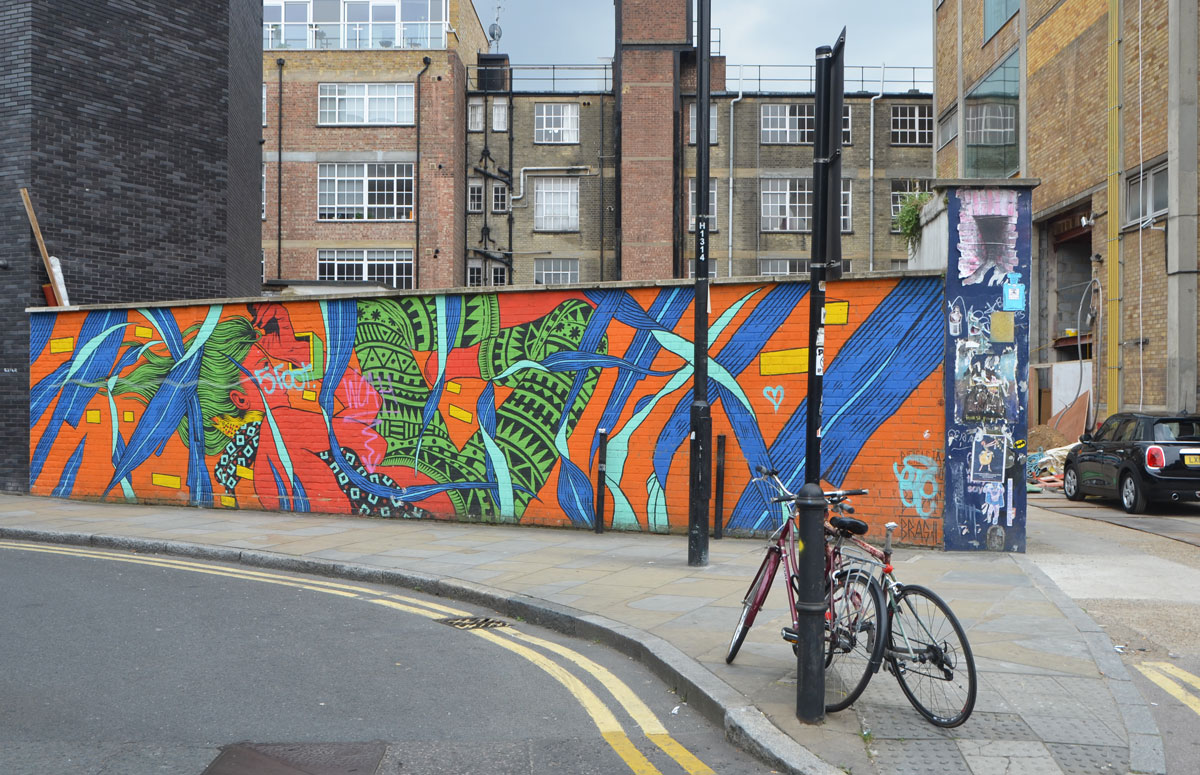 mural by bicicletas on a low brick fence on a street, low rise apartments in the background, a bike parked in front.  Bright and bold colours, red, blue, green and orange mostly, abstracted nature scene