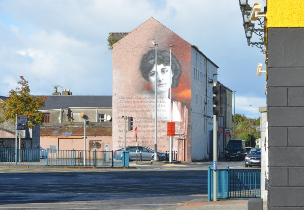 a mural covers the side of a multistorey building, a woman's head and lines of poetry, When you are old by William Butler Yeats.