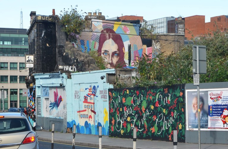 murals on a wall and on the upper storey of a pub behind the fence, a tug boat, fowers, a woman's head
