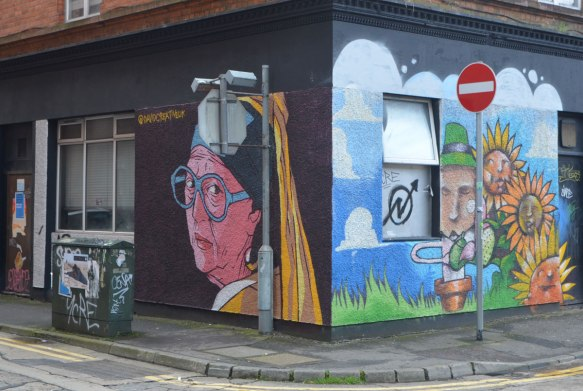 two murals on a corner of a building. One one sideis a head and shoulders of a nun in a yellow habit with black head wear. On the other corner is a leprechaun and some sunflowers.