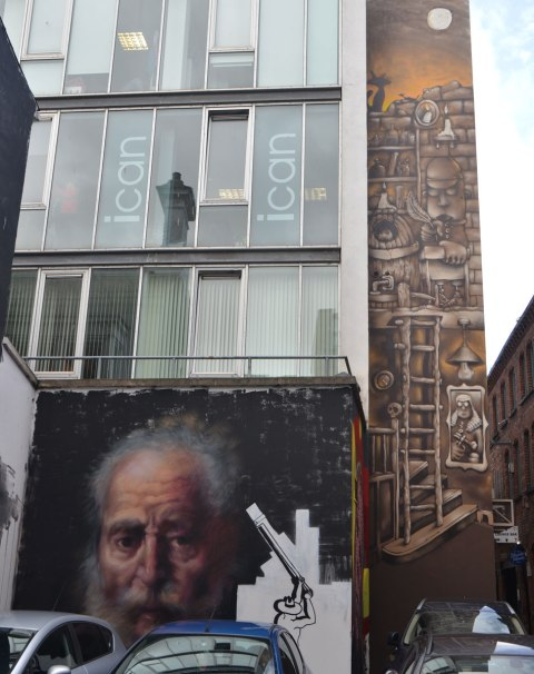 two murals on a building, one is a very realistic painting of an old man and the other is a vertical painting in brown tones by KVLR