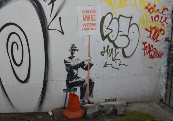 stencil of a man sitting on a stool, wearing a suit and hat, and holding a sign with red letters on white that say Once we were heroes.