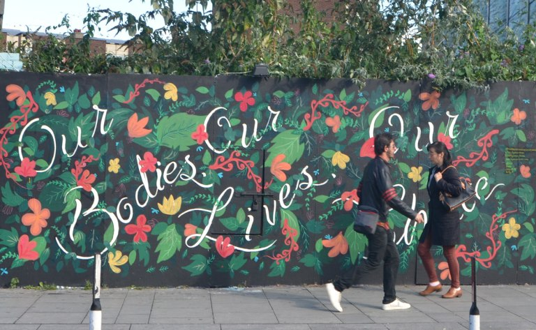 two people walking past a mural covered with pictures of flowers and leaves and the words, in cursive writing, Our bodies our lives our choice