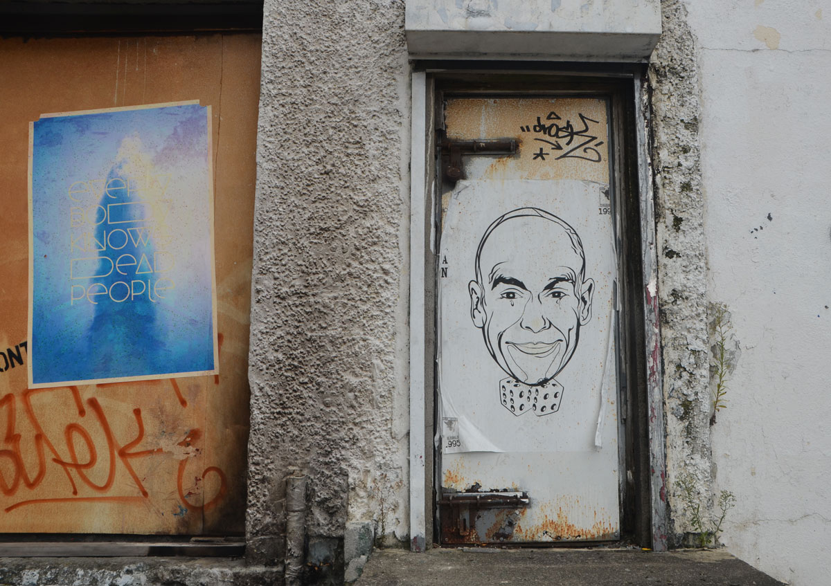 large paste up of a man's head on a door of a grubby dirty white wall.