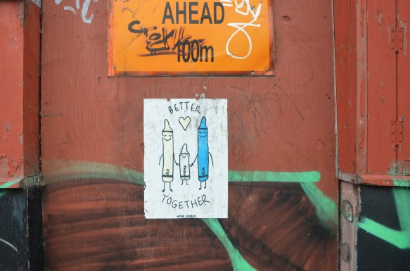 a poster of three crayons standing together and holding hands. The one in the middle is purple and it's shorter, On either side is red and blue. At least that's what the words say, only the blue has been coloured in, signed #peachydublin
