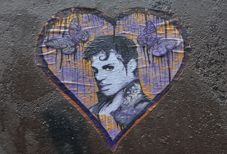 a paste up street art piece in tribute to the musician Prince, his head in profile in a heart with purple accents