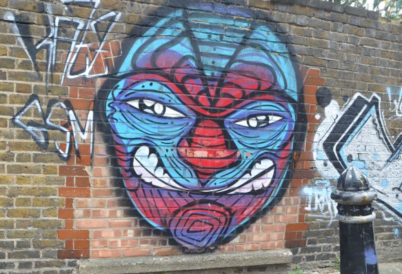 street art painting on a brick wall of a large face in red and blue with some whites in the eyes and some white teeth.