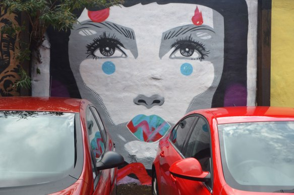 two red cars are parked against a wall on which a mural of a young woman's face is painted. white skin, black hair, grey eyes,