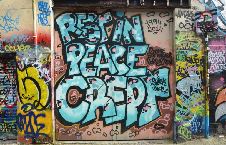 large text graffiti that says rest in peace crept that covers a garage door.