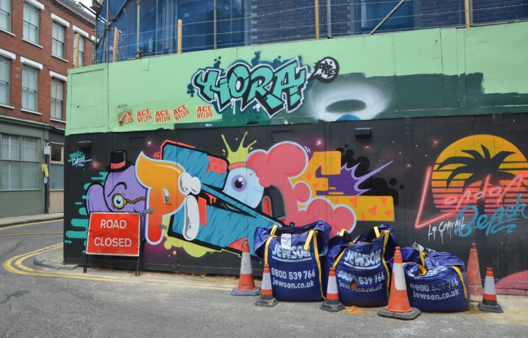construction hoardings covered with street art, a Road closed sign is in front.