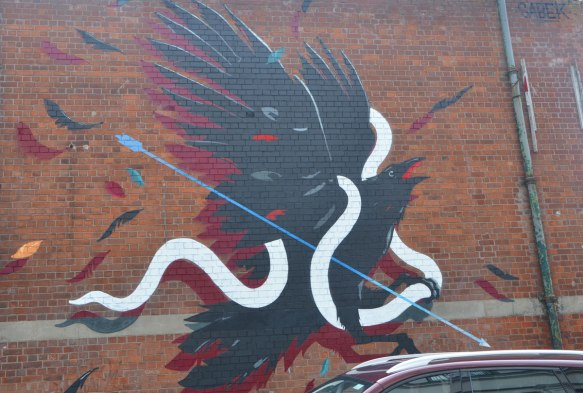 mural by sabek of a black bird caught up in a white ribbon as it tries to fly