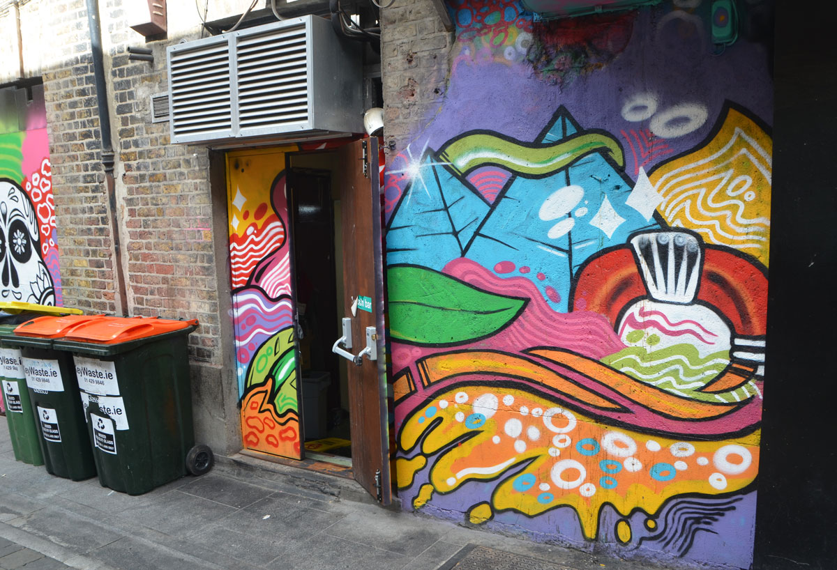 abstract painting street art on the side of a building and over the door, many colours and shapes