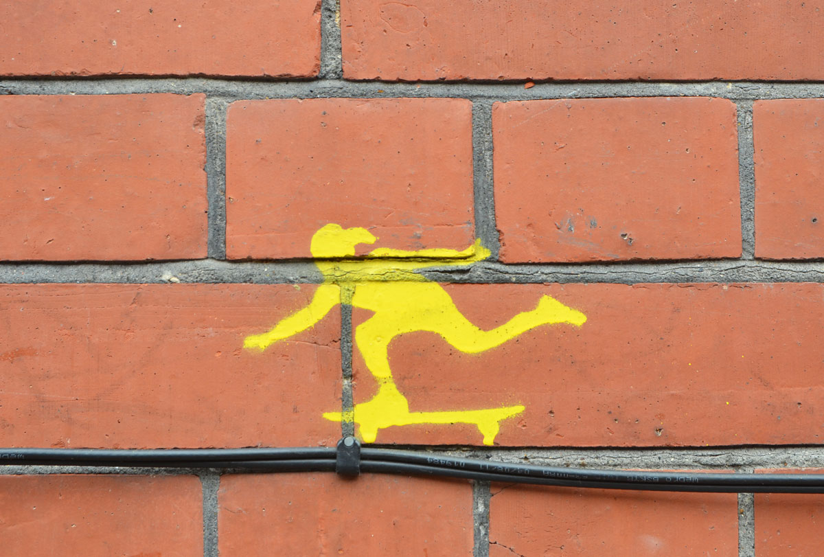 little yellow stencil of a person skateboarding, on a brick wall