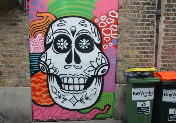 a metal street box is covered with a colourful painting of a shite skull decorated like Mexican day of the dead on a many patterened background.